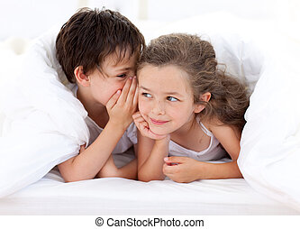 Siblings playing on parent\'s bed
