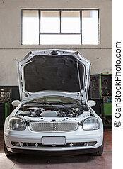car repair - car with the hood open in repair workshop
