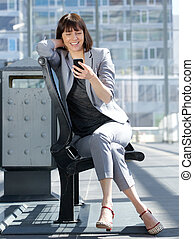 Smiling business woman reading text message on mobile phone...