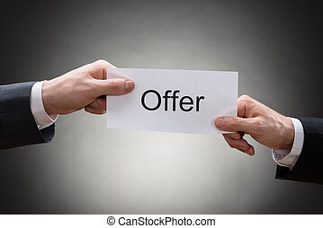 Close-up Of Two Hands Holding Paper With Text Offer -...
