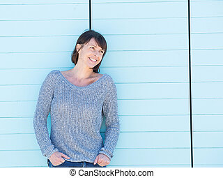 Smiling woman standing against blue background - Portrait of...