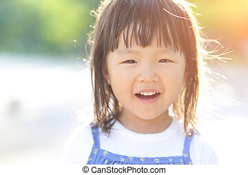Happy Cute little girl on the meadow in summer day, asian