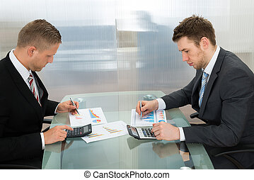 Two Businessman Analyzing The Graph - Two Young Businessman...