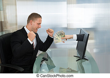 Excited Businessman With Money Coming Out From Computer Screen