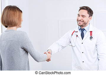 Nice doctor shaking hands with the patient - Good bye....