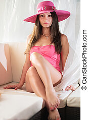 Young sexy brunette wearing pink top and hat sitting on the...