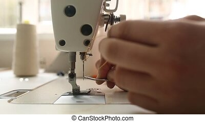 person inserts a needle thread - man preparing industrial...