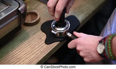 Barista presses the coffee for espresso