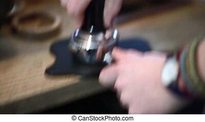 Barista presses the coffee for espresso (old fashion)