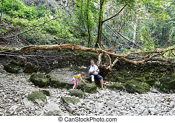 Little girl climbing stones, showing off to her mother -...
