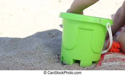 Sand Toy Bucket - A green plastic pail used as a toy on the...