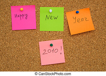 Adhesive paper note on cork board with words Happy New Year...