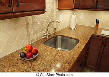 Stainless steel sink in a remodeled kitchen with a quartz...