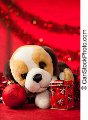 Toy dog with christmas ornaments over red