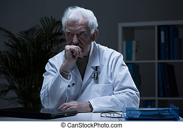 Sitting after work - Elderly physician sitting alone in his...
