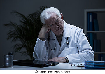 Doctor with depression - Aged doctor with depression sitting...
