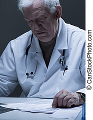 Checking the test results - Older worried doctor checking...