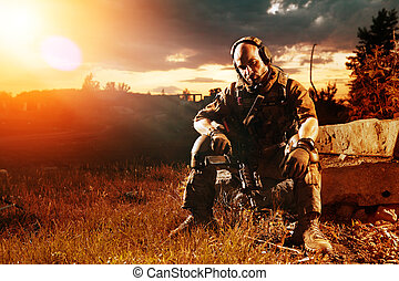 American soldier with the M4 rifle is having a rest Sunset...