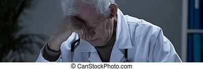 Melancholic old man with burnout sitting at work