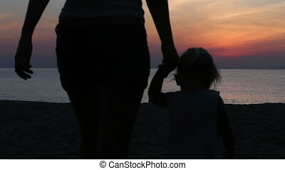 silhouette of mother and daughter going to sea at sunrise