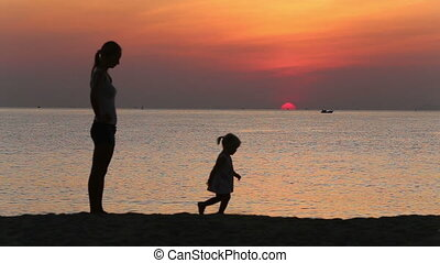 silhouette of daughter running away from mother at sunrise
