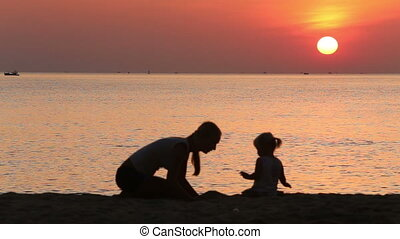 silhouette of mother and toddler building castle at sunrise