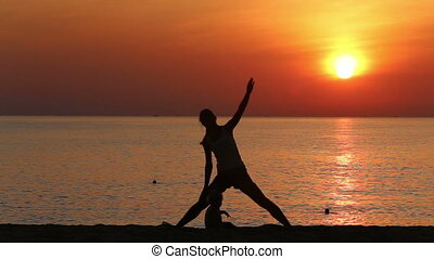 silhouette of mother doing exercises at sunrise above sea