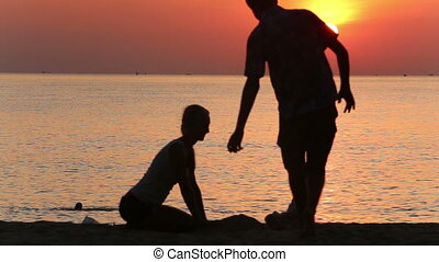 silhouette of father swinging daughter by hands at sunrise