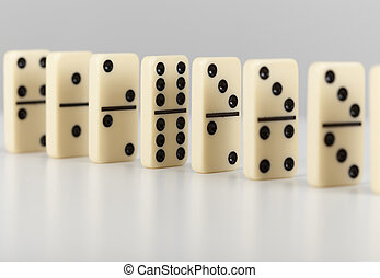 Dominoes line up on a grey surface