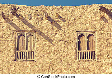 Two arc windows on an old  rouch stone wall.
