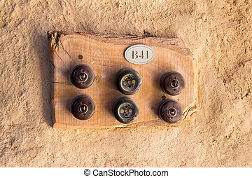 Two old sockets and four switches on ? wooden plate.