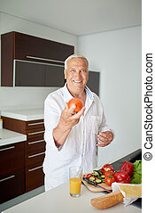 man cooking at home preparing salad in kitchen - Handsome...