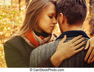 Young woman embraces a man, couple in love