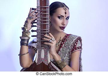 Beautiful Indian Woman in Sari with Oriental Jewelry Posing with Sitar