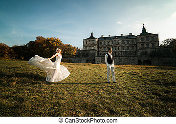 beautiful couple having fun on the lawn in front of the...