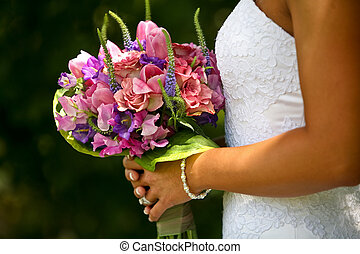 Bouquet - A half-body view of a bride holding up a bouquet