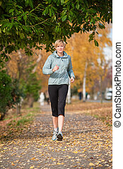 Runner - A young woman running on a path