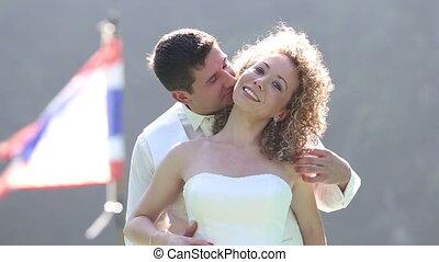 groom speaks in brides ear and tickles against flag -...