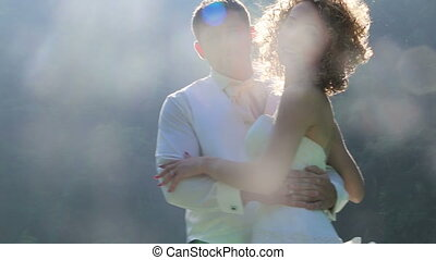 bride in downy dress hugs groom against backlight and stains...