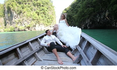 european bride and groom sit in longtail boat - curly blonde...