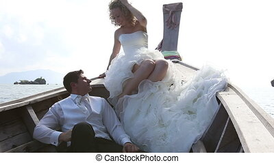 groom and blonde bride in downy talk in longtail boat -...