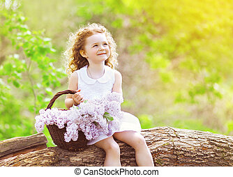 Little girl with basket of lilac flowers sitting and...
