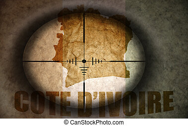 sniper scope aimed at the vintage ivorian flag and map
