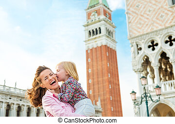 Laughing mother being kissed by daughter on St Marks Square...