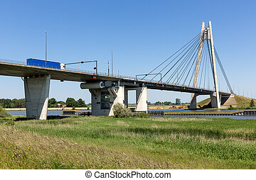 River IJssel with bridge near Kampen in The Netherlands -...