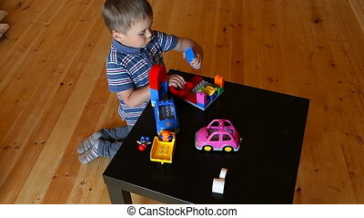 Cute boy plaing with toy car on floor, isolated on white