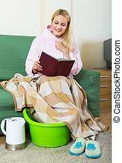 Blonde taking foot bath at home - Young smiling blonde woman...