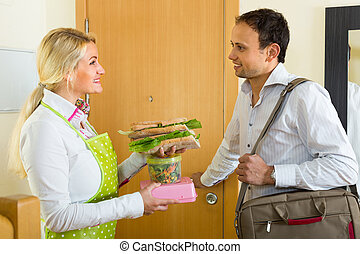 Housewife preparing sandwich for husband - Happy smiling...