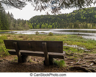 Old wooden bench by lake in hills
