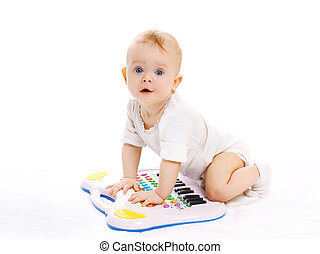 Portrait of curious baby playing with toy piano